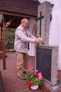 Znicz zapala Zenon Brzóska, organizator wyjazdu do Oświęcimia